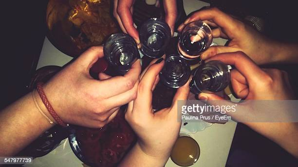 Close-Up Of Hands Toasting Shot Glasses In Restaurant