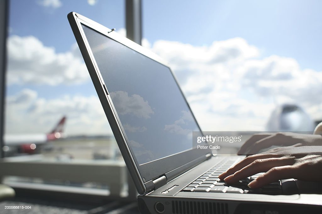 Close-up of hands using laptop in airport : Stock Photo