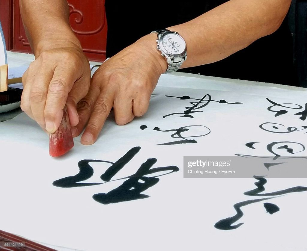 Close-Up Of Hands Writing Chinese Calligraphy