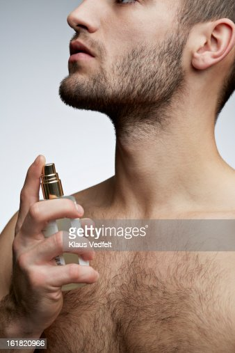 Close-up of handsome man spraying perfume : Stock Photo