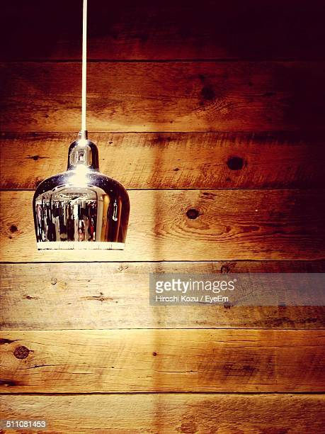 Close-up of hanging light against wooden wall
