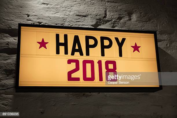 Close-up of Happy 2018 signboard against gray wall