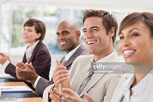 Closeup of happy businesspeople clapping hands