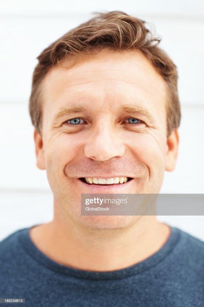 Closeup of happy mature man smiling over a wall
