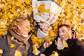 Close-up of happy parents and daughter among autumn leaves.