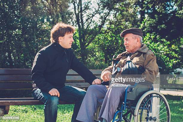 Close-Up of Happy Senior Man in Wheelchair and Grandson Outdoors
