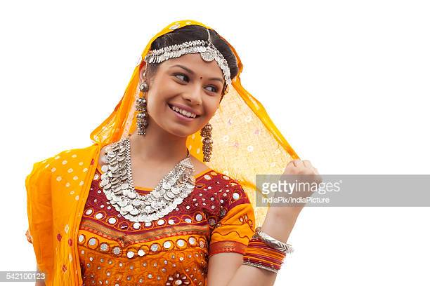 Close-up of happy young woman wearing choli and dupatta over white background