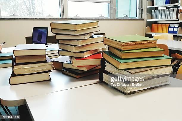 Close-Up Of Hardcover Book Stacks On Table In Library