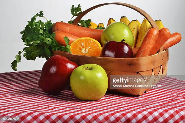 Close-Up Of Healthy Food Basket On Table Against White Wall