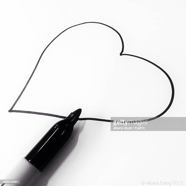 Close-up of heart shape and felt tip pen on white background