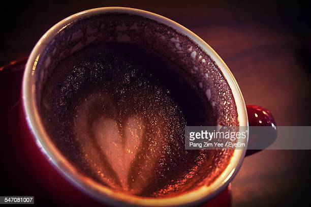 Close-Up Of Heart Shape Froth Art On Cappuccino Served On Table