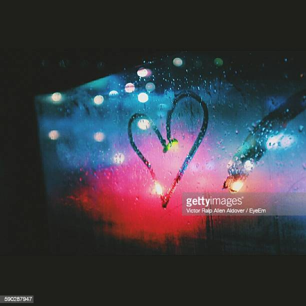 Close-Up Of Heart Shape On Condensed Windshield In Rain