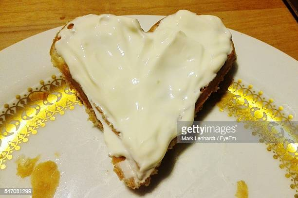 Close-Up Of Heart Shape Waffle Covered With Cream Served On Table