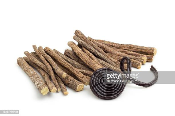 Close-Up Of Herb Sticks Over White Background
