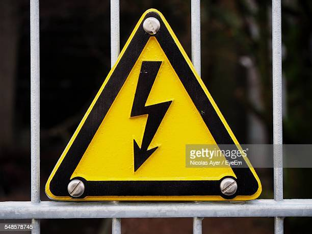 Close-Up Of High Voltage Sign Board On Metal Gate