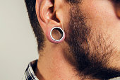 Closeup of hipster ear, with hole earring, gauge earring male