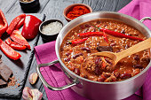 hot delicious chili con carne with whole red hot chilis, kidney beans, tomatoes and piece of chocolate in a pot with ingredients at background, authentic recipe, view from above, close-up