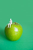 Close-up of human figurine sitting on green apple over colored background