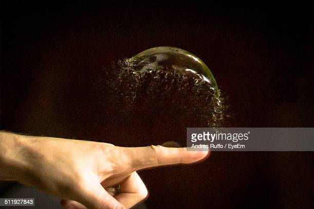 Close-up of human finger breaking soap bubble over black background
