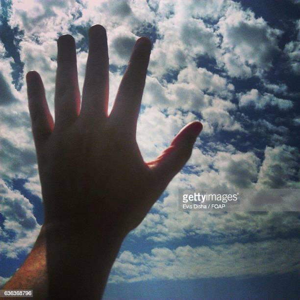 Close-up of human hand against cloudy sky