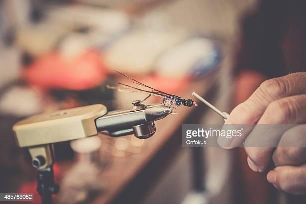 Primo piano della mano umana creare Fly esca da pescatore