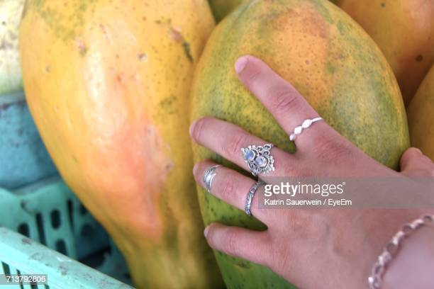 Close-Up Of Human Hand Holding Papaya