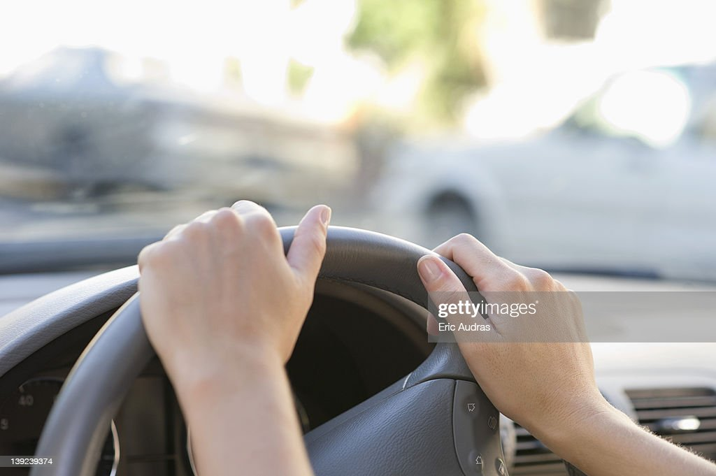 Close-up of human hand holding steering wheel