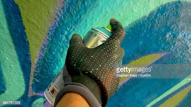 Close-Up Of Human Hand Spray Painting Wall