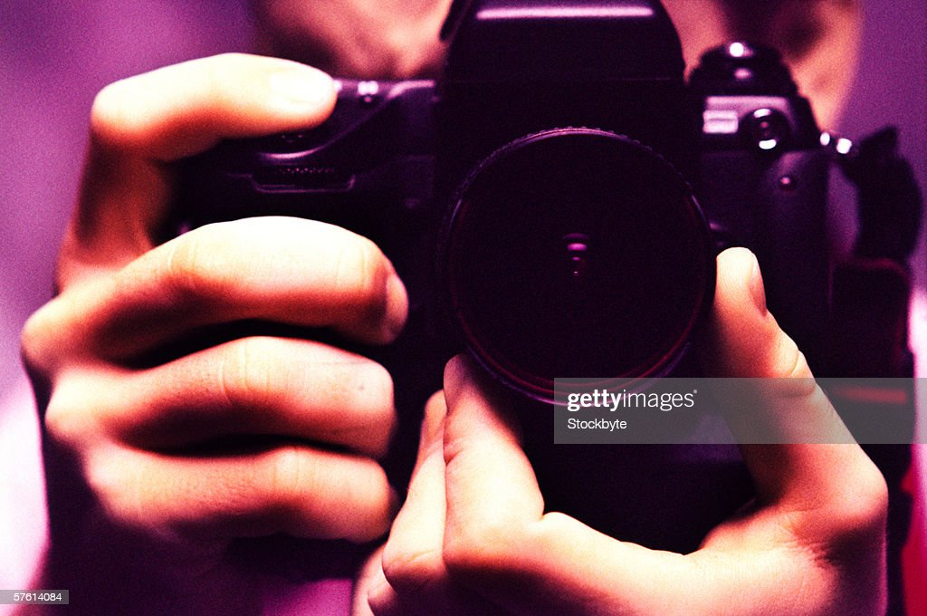Close-up of human hands holding a camera (toned) : Stock Photo