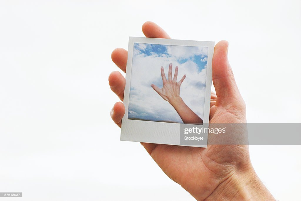 Close-up of human hands holding photograph : Stock Photo