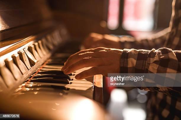 Gros plan des mains de l'Homme jouant du piano.