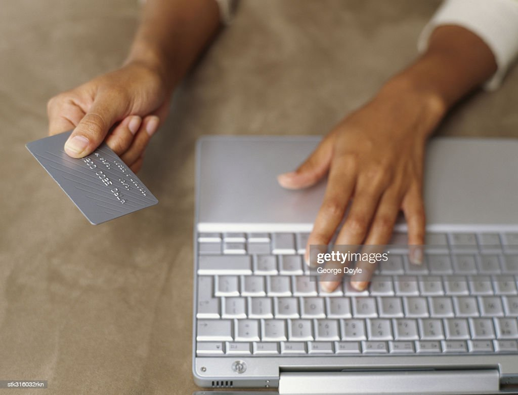 close-up of human hands working on a laptop and holding a credit card : Stock Photo