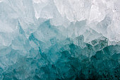a close up of a small ice cave on top of a glacier, shows the ice crystals and the deep blue color of the ice.