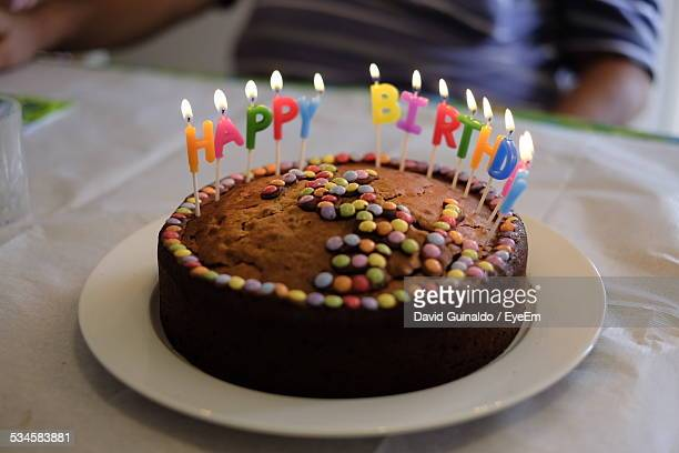Close-Up Of Illuminated Birthday Candles On Cake