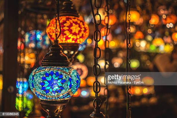 Close-Up Of Illuminated Decorative Lanterns Hanging In Shop