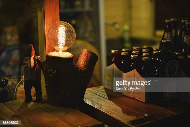 Close-Up Of Illuminated Electric Bulb On Wood At Table