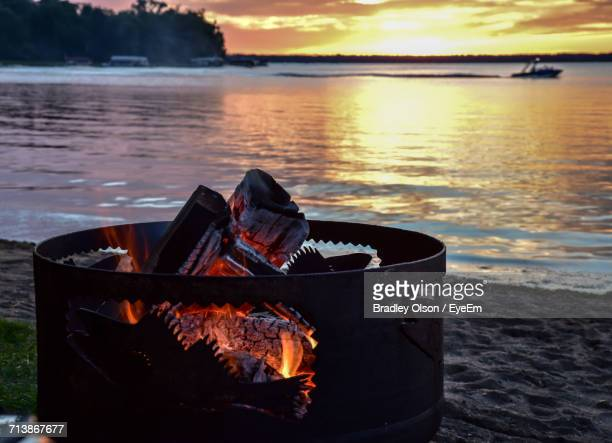 Close-Up Of Illuminated Fire Pit At Beach During Sunset