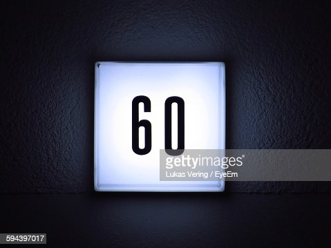 Close-Up Of Illuminated House Number On Wall