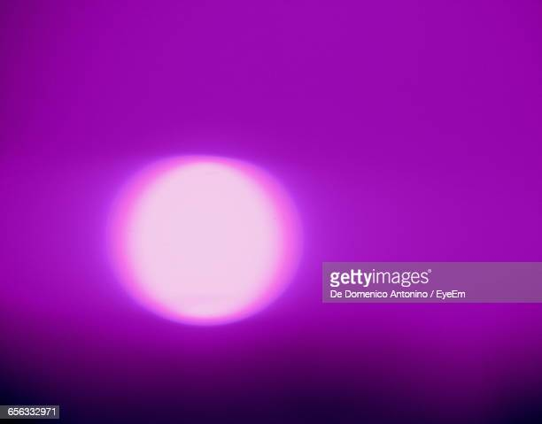 Close-Up Of Illuminated Light Against Purple Background