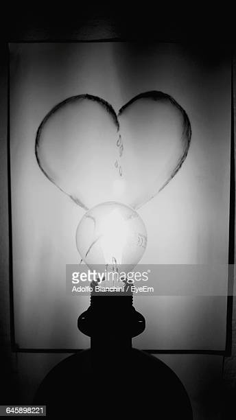 Close-Up Of Illuminated Light Bulb Against Heart Shape Painting