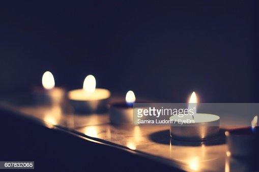 Close-Up Of Illuminated Tea Light Candles On Table In Darkroom