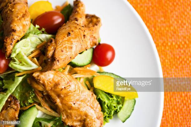 Close-up of Indian spiced chicken dish with salad