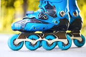 Close up of inline roller skates with blue wheels.