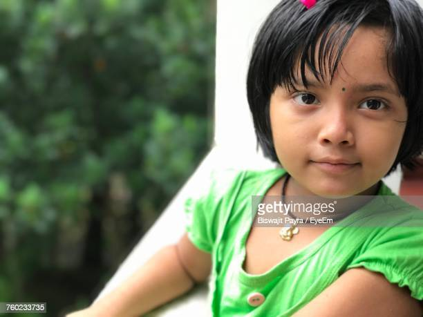 Close-Up Of Innocent Girl Looking Away While Standing In Balcony