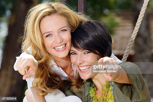 Closeup of Italian actresses Francesca Cavallin and Barbara Livi smiling and pointing their forefinger at the camera in a photo shooting on the set...