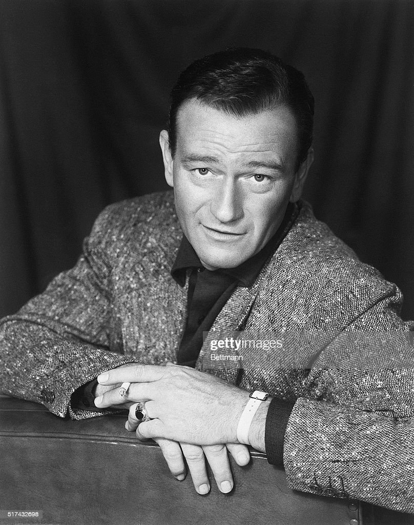 Closeup of John Wayne (1907-1979) American actor. He is shown seated, facing the back of the couch on which he is seated. Ca. 1940s-1950s.