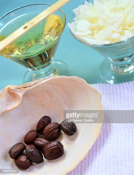 Close-Up Of Jojoba Seeds With Oil And Flakes On Table
