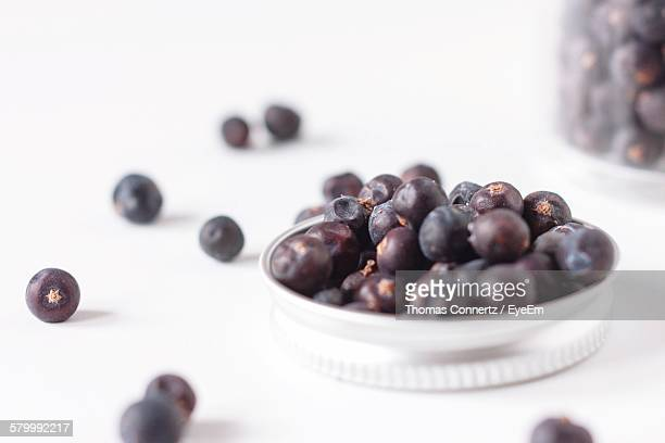 Close-Up Of Juniper Berries In Container Against White Background