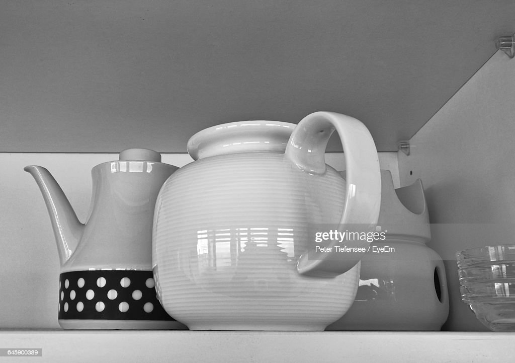 Close-Up Of Kettles On Shelf