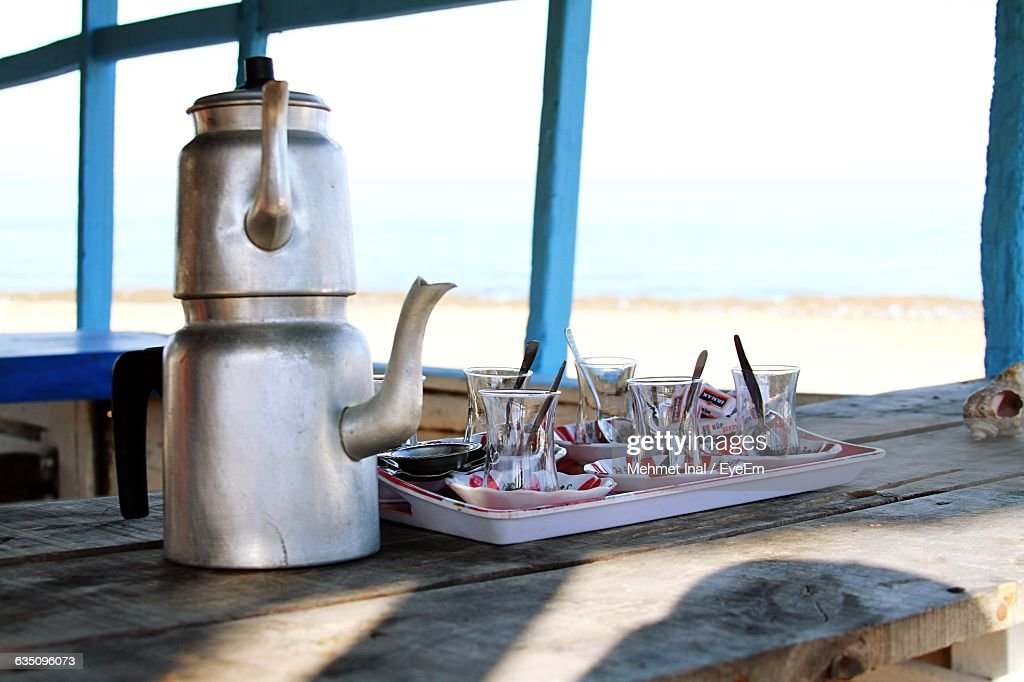 Close-Up Of Kettles With Glasses On Table